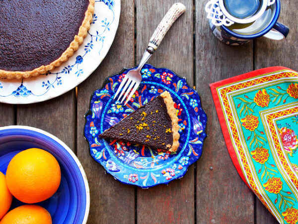 Overhead view of a slice of chocolate orange tart on a dark blue floral plate surrounded by a colorful cloth, a cup of tea, the rest of the tart on a white and blue plate, and a bowl of oranges.