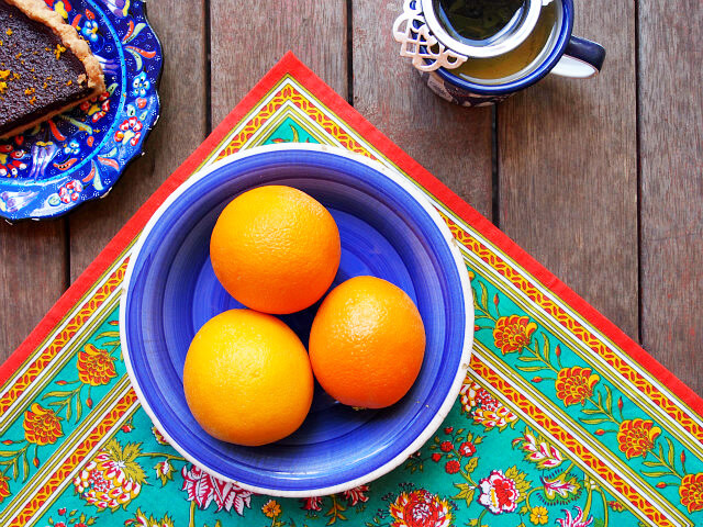 Overhead view of three oranges in a blue bowl sitting on a brightly colored floral cloth next to a cup of tea and a slice of chocolate orange tart.