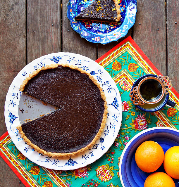 Overhead view of a chocolate orange tart on a white and blue floral plate, with a slice cut out and plated on a dark blue dish, a cup of tea, and a bowl of oranges on a brightly colored floral cloth.