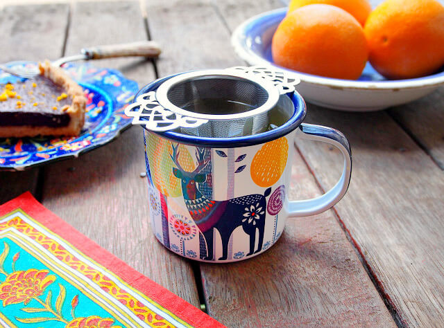 A colorful mug of tea with a deer on it sits on a wooden table. In the background is a bowl of oranges and a slice of chocolate orange tart.