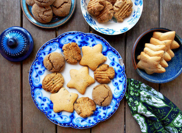 Overhead view of blue and white plates full of cookies made with tea arranged on a wooden table.