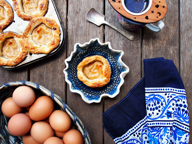 Overhead view of a Portuguese egg tart on a handmade dish, surrounded by eggs, a tea towel, a cup of tea, and a pan with more tarts on a wooden table.