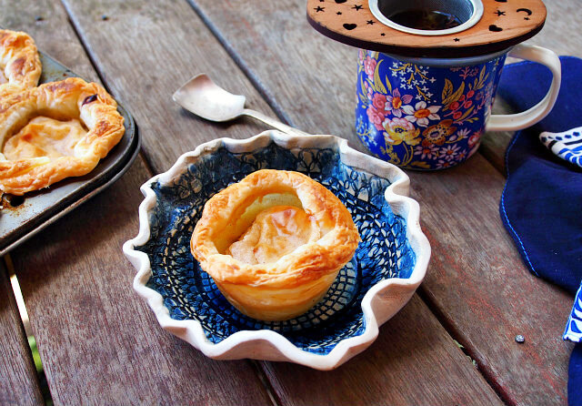 A Portuguese egg tart sits on a handmade blue and white dish next to a floral mug of tea on a wooden table.