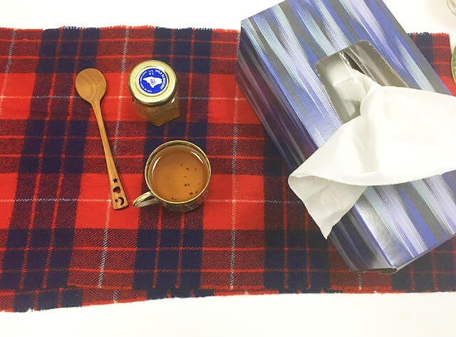 Overhead view of a cup of tea, jar of honey, wooden tea spoon, and box of tissues arranged on a red and blue plaid table runner.