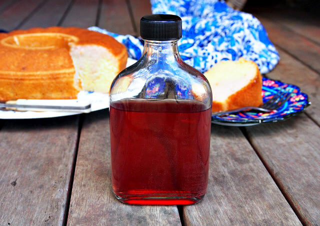 A bottle of homemade hibiscus liqueur stands on a wooden table.