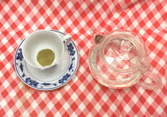 Overhead view of a clear glass teapot and a white and blue teacup with matcha powder in the bottom, all on top of a red and white checkered tablecloth.