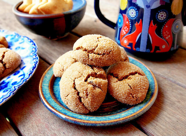 A stack of molasses cookies made with tea sits on a handmade plate next to a mug of tea.