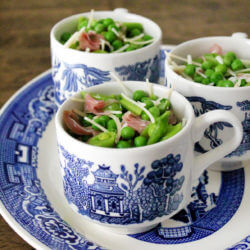 Three blue and white mugs filled with the best pea salad recipe ever are displayed on a blue and white platter on a wooden table.