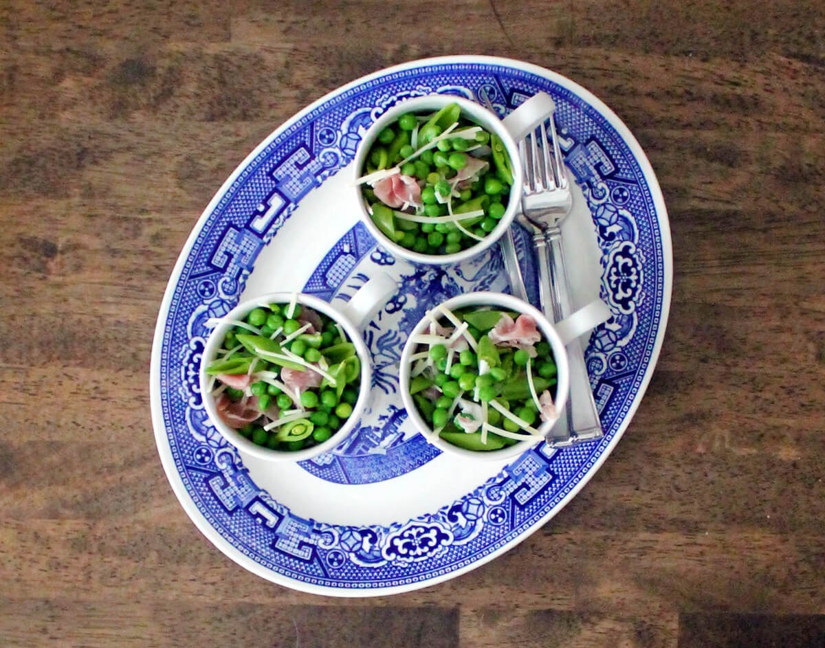 Overhead view of three mugs filled with the best pea salad recipe ever on a blue and white platter resting on a wooden table.