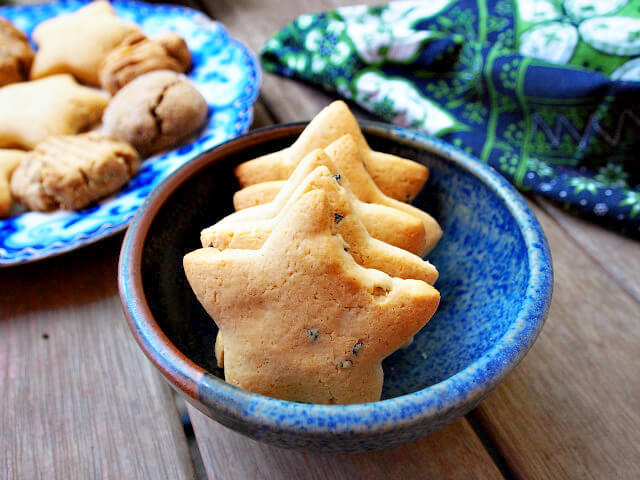 Star-shaped sweet milk cookies made with tea are displayed in a handmade pottery bowl on a wooden table.