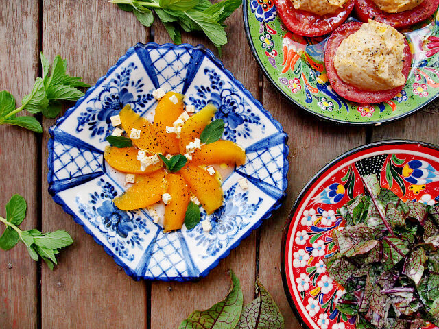 Overhead view of an orange and feta cheese tea party salad on a blue and white plate.