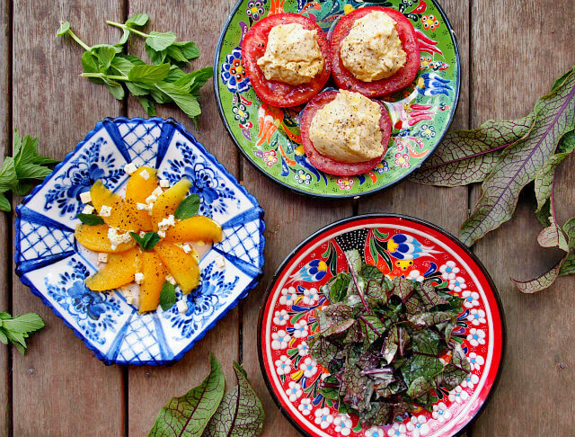 Overhead view of three tea party salads on brightly colored floral plates on a wooden table, surrounded by greens.