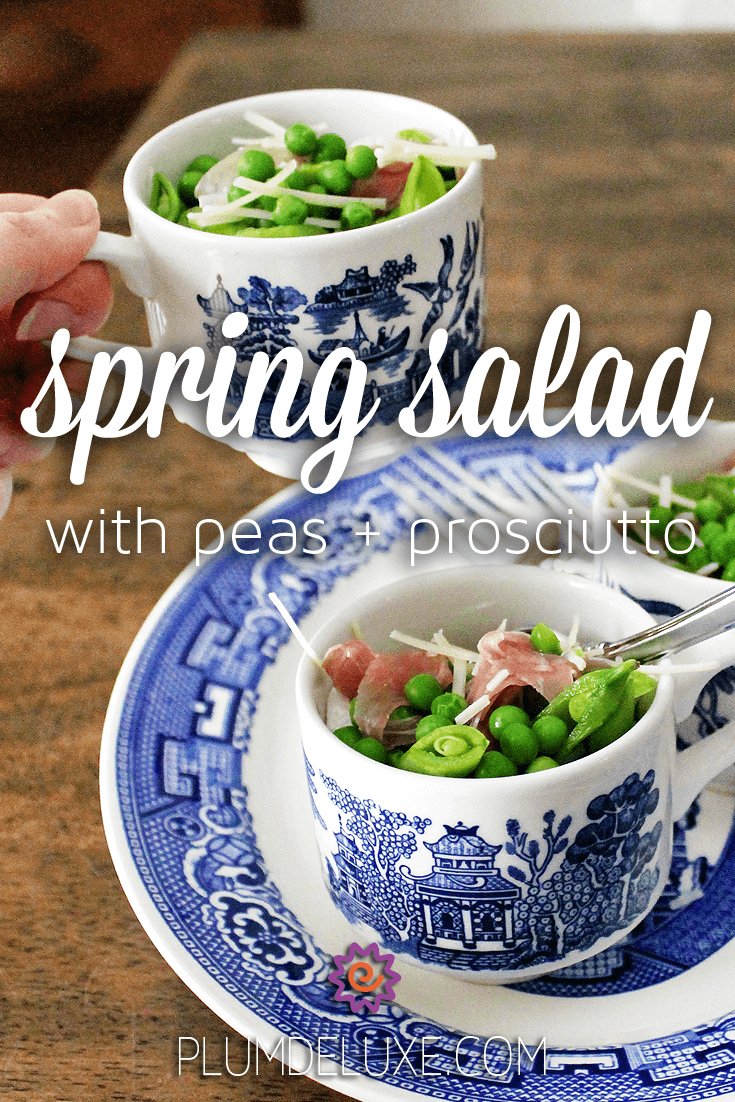 A hand picks up a blue and white mug full of the best pea salad recipe ever from a plate of mug filled with salad.