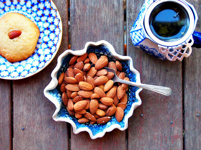 Overhead view of a bowl of almond, with a cup of tea and almond tea cookie on the side.