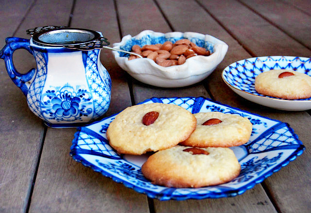 Almond tea cookies sit on a blue and white plate with a cup of tea and a bowl of almonds in the background.