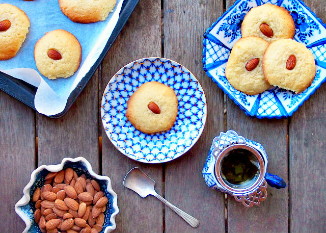 Overhead view of almond tea cookies on plates and a baking tray, with a bowl of almond and cup of tea on the side.
