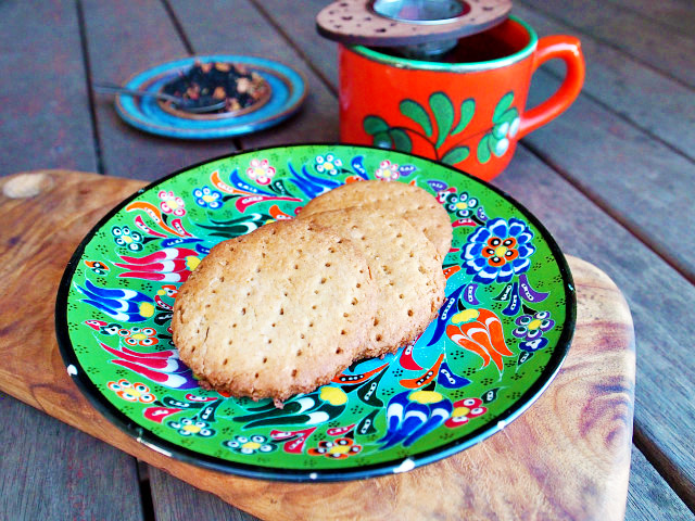 Three English tea biscuits are arranged on a green floral plate next to a red mug of loose leaf tea on a wooden table.
