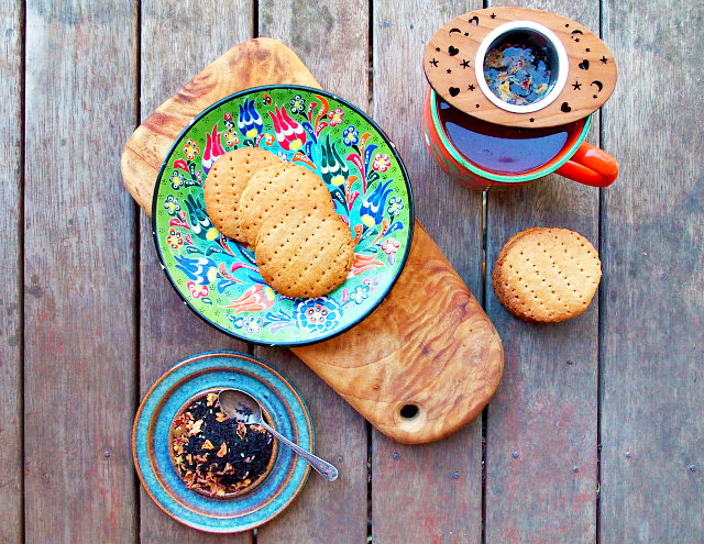 Overhead view of a stack of English tea biscuits recipe on a green floral plate surrounded by a cup of tea, loose leaf tea, and more biscuits on a wooden table.
