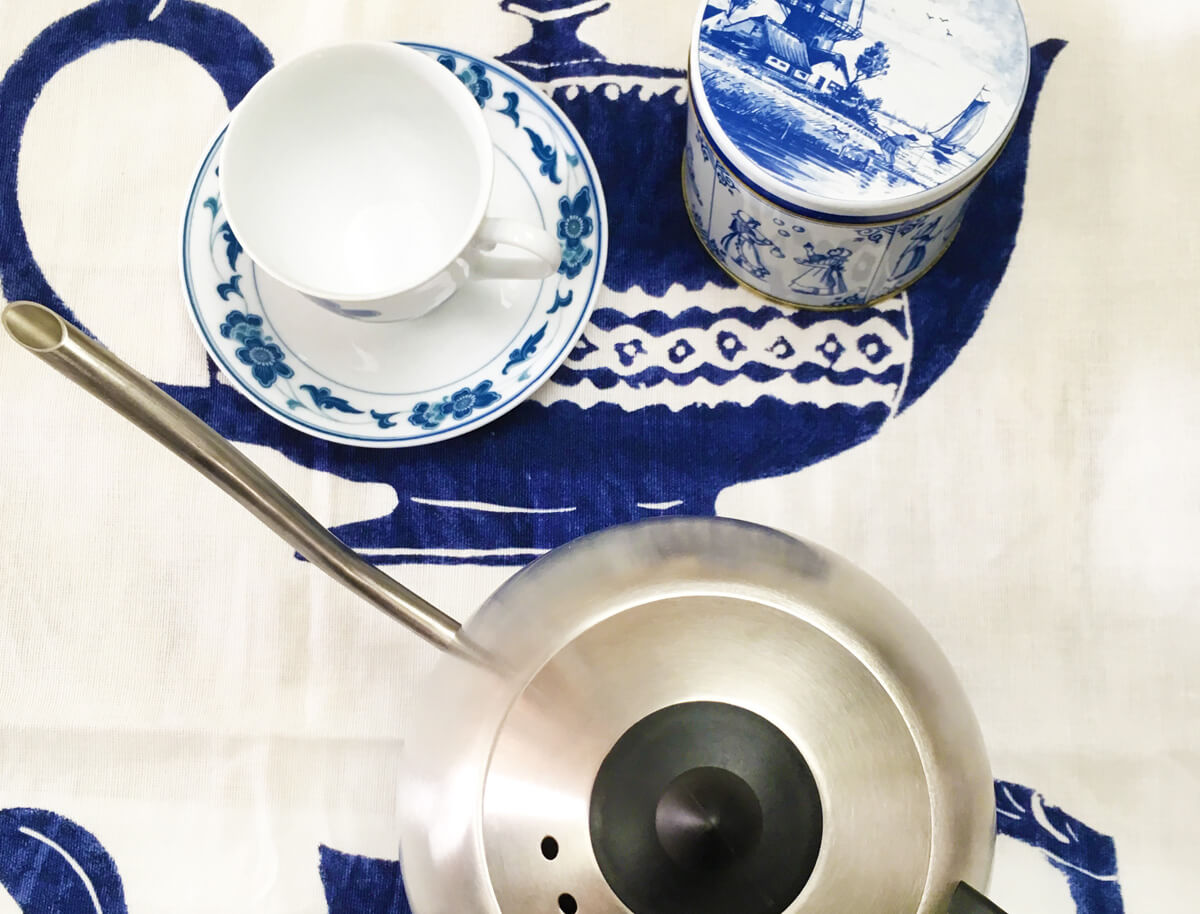 Overhead view of a white and blue tea tin and floral teacup along with a stainless steel kettle arranged on a white and blue teapot print cloth.