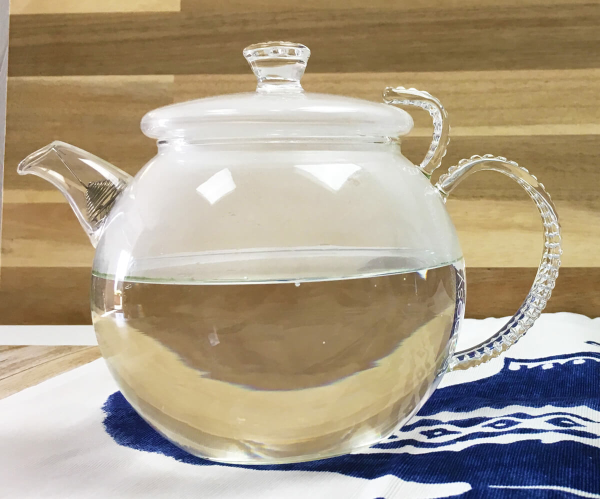 A clear glass teapot full of boiling water sits on a white and blue tea towel.
