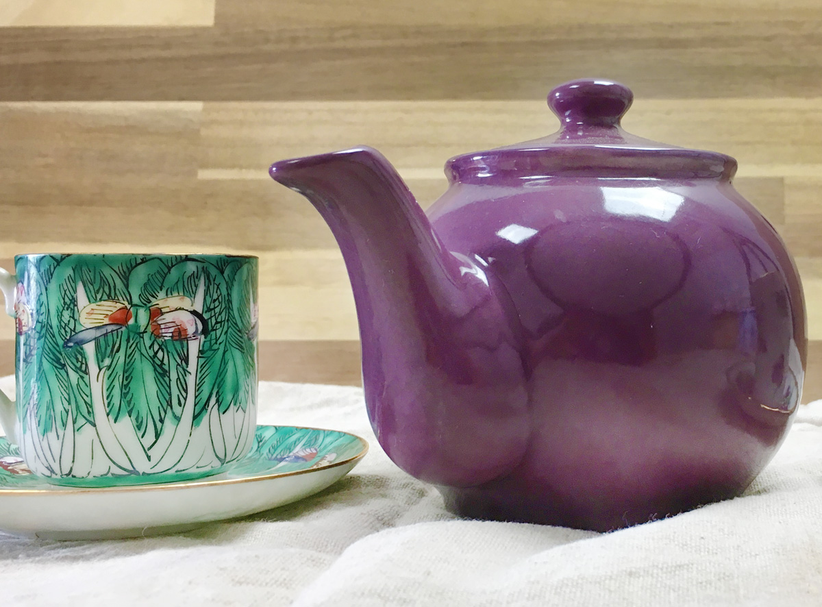 A purple teapot sits next to a green floral teacup on a linen cloth.