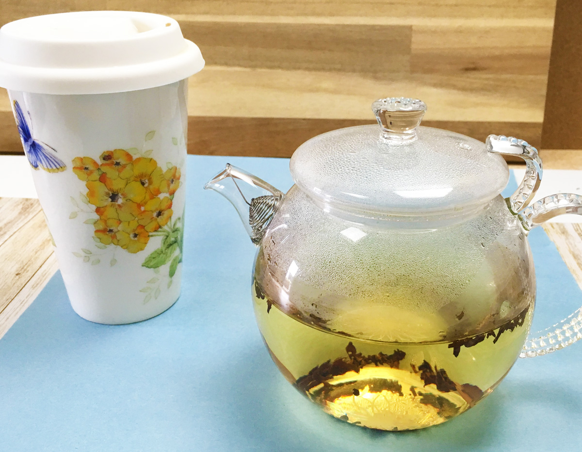 A clear glass teapot full of keto friendly herbal tea and a white floral travel mug sit side by side on a blue mat.