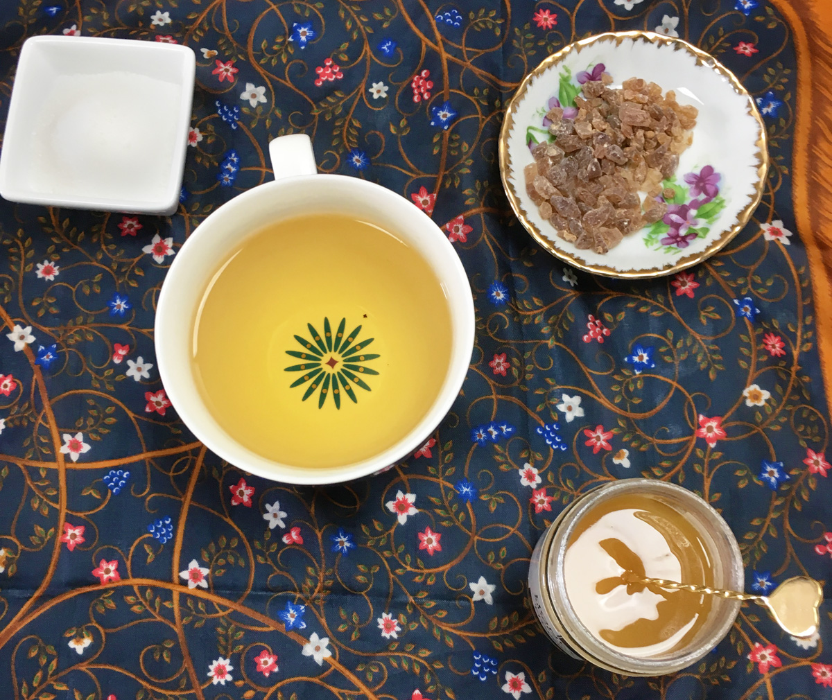 Overhead view of a cup of unsweetened tea surrounded by a jar of honey and two bowls of sugar on a dark blue floral print cloth.