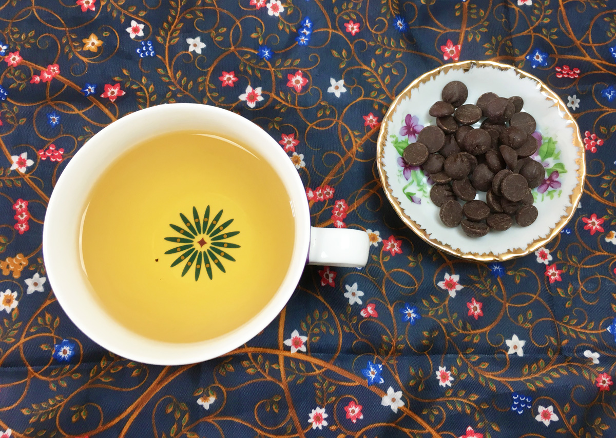 Overhead view of a mug of tea next to a small plate of chocolate chips on a blue floral print cloth.