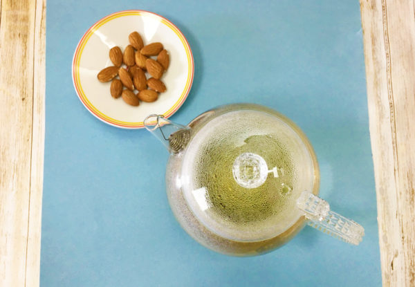 A clear glass teapot full of green tea and a white dish of almonds sit on a blue mat.