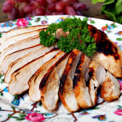 Closeup view of a plate of sliced chicken breast covered in a tea marinade for chicken.