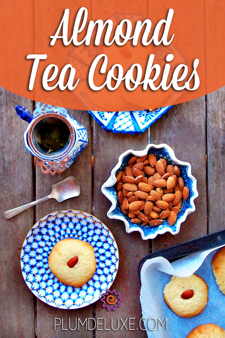 Overhead view of almond tea cookies on a baking tray and plate with a bowl of almonds and a cup of tea.