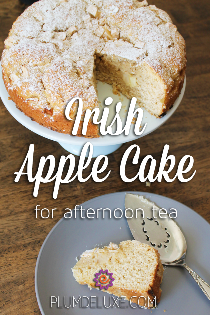 An Irish apple cake sits on a white cake stand with a slice of cake on a gray plate next to it.