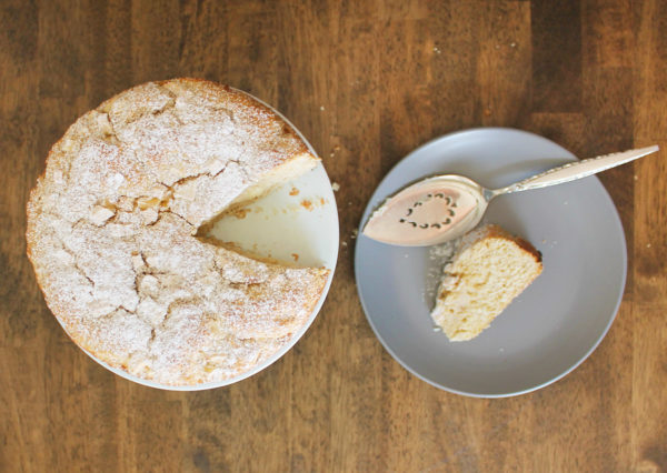 Overhead view of an Irish apple cake with a slice cut out of it. The slice sits on a gray plate to the side.