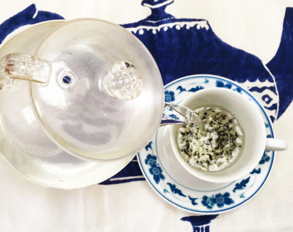 Overhead view of boiling water being poured from a clear glass teapot into a white and blue teacup.