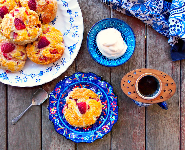 Overhead view of a plate of British strawberry scones with whipped heavy cream and a cup of tea, all in blue floral dishware on a wooden table.