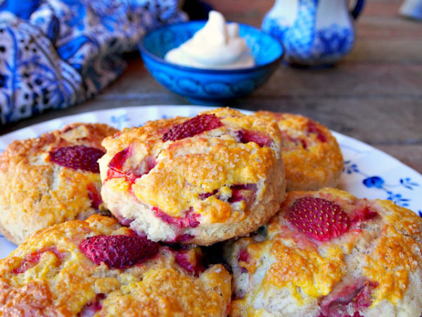 Closeup of a pile of British strawberry scones on a white and blue plate.