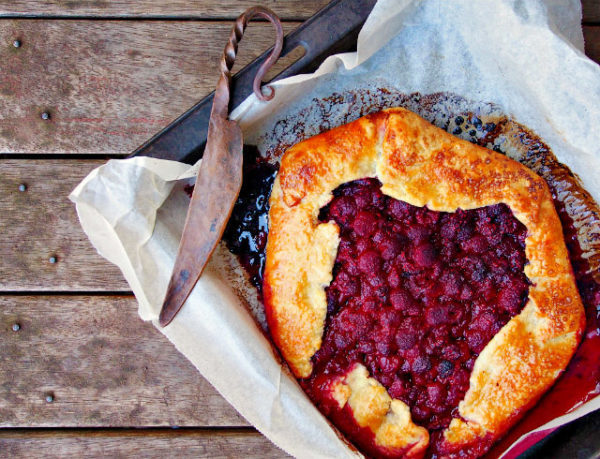 Overhead view of a raspberry galette with tea syrup on a baking tray.