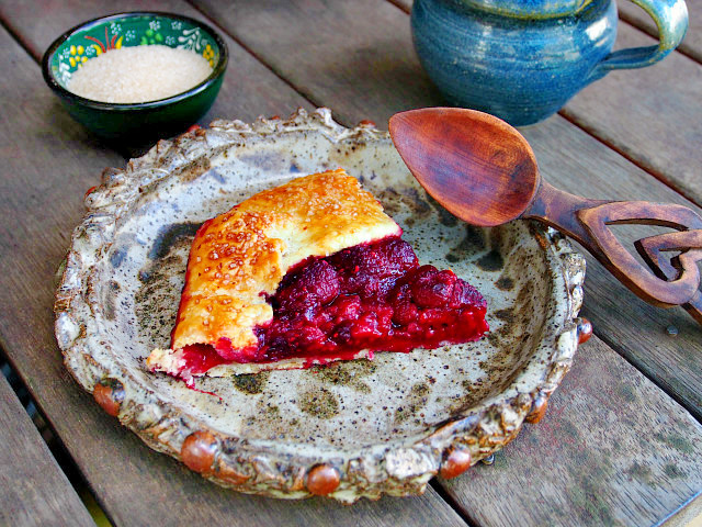 A slice of raspberry galette with tea syrup sits on a handmade pottery plate next to a wooden spoon.
