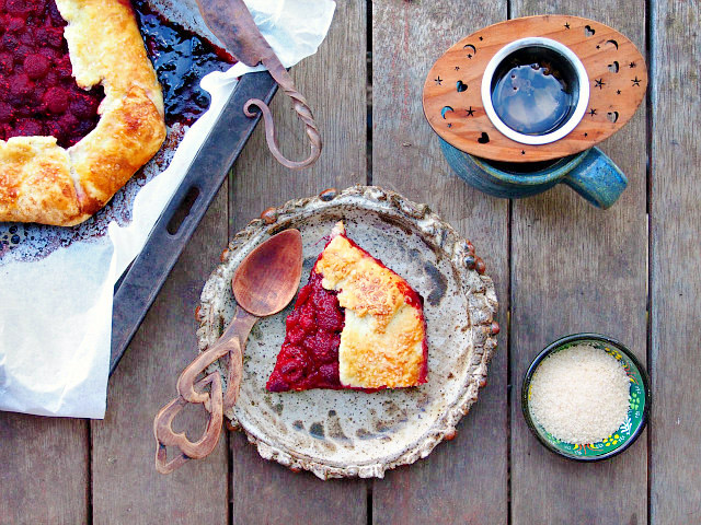 Overhead view of a raspberry galette on both a baking tray and a slice on a small plate, with a cup of tea on the side.