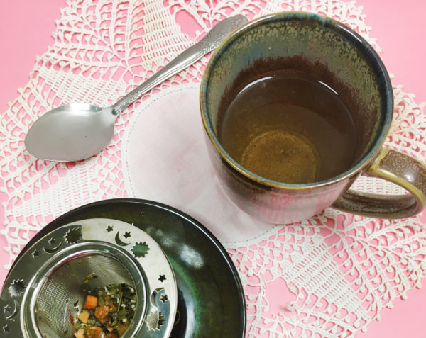 A mug of tea sits next to a tea infuser full of spent tea leaves on top of a white doily on a pink tablecloth.