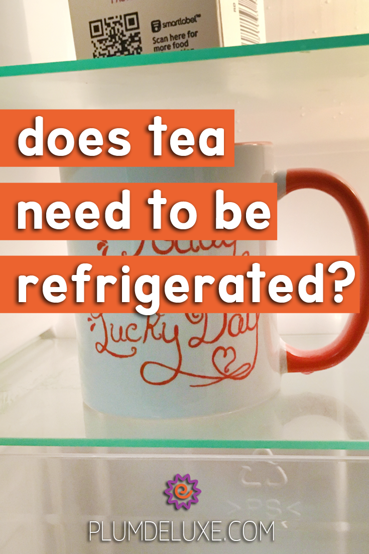 A cup of tea sits on a shelf in a refrigerator.