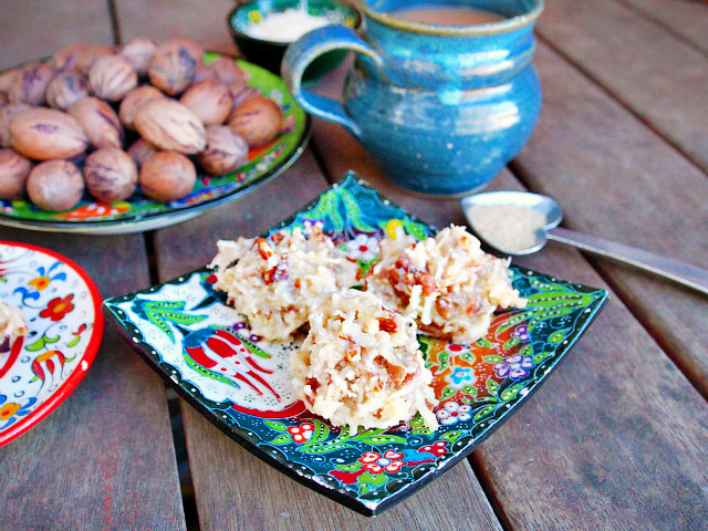 Three coconut praline pecans sit on a floral plate in front of a mug of tea and a plate full of pecans.