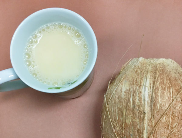 Overhead view of a white mug full of bulletproof tea recipe next to a coconut on a mauve background.