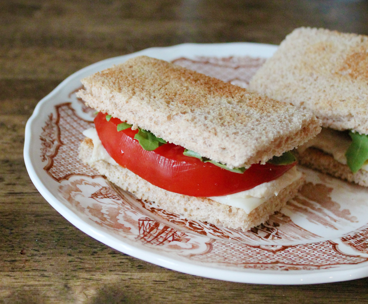 Closeup of a tomato finger sandwich on a brown and white plate.