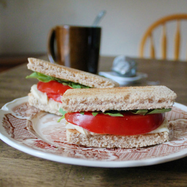 Two tomato tea sandwiches sit on a brown and white plate with a brown mug full of tea in the background.