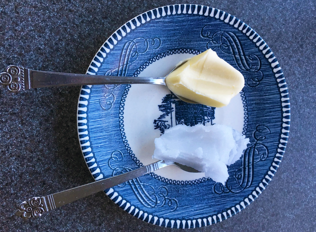 Overhead view of spoons full of butter and coconut oil resting in a blue and white dish.