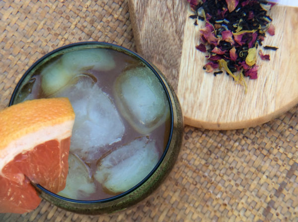 Overhead view of a glass of iced black tea with a wedge of grapefruit next to a pile of loose leaf black tea on a wooden board.