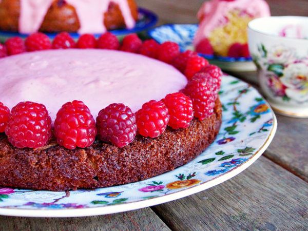 Closeup side view of a summer raspberry cake topped with Norwegian raspberry snow and fresh raspberries.