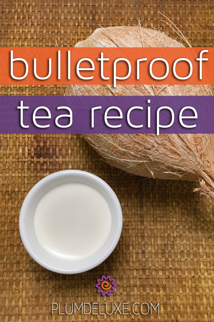 Overhead view of a white mug full of bulletproof tea recipe next to a coconut on a woven tray.