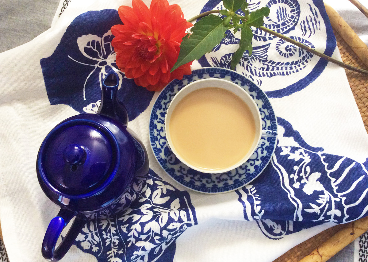 Overhead view of a blue and white teacup full of tea, a blue teapot, and an orange flower arranged on a white and blue tea towel.